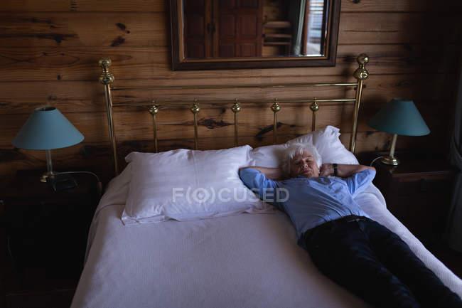 Visão de alto ângulo de uma mulher idosa ativa dormindo na cama com as mãos atrás da cabeça no quarto em casa — Fotografia de Stock