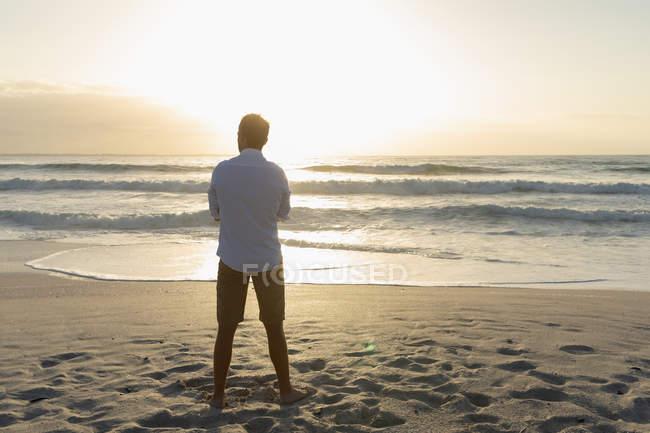 Rückansicht eines entspannten Mannes, der an einem sonnigen Tag am Strand steht. er beobachtet den Sonnenuntergang auf dem Ozean — Stockfoto