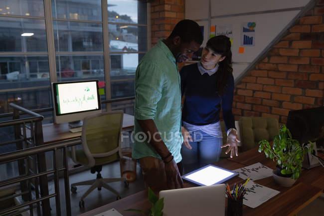 Vue de face des gens d'affaires diversifié discutant sur une tablette numérique avec l'autre dans le bureau — Photo de stock