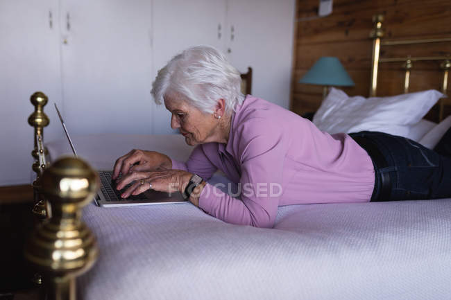 Side view of an active senior woman lying on her bed and using a laptop in bedroom at home — Stock Photo