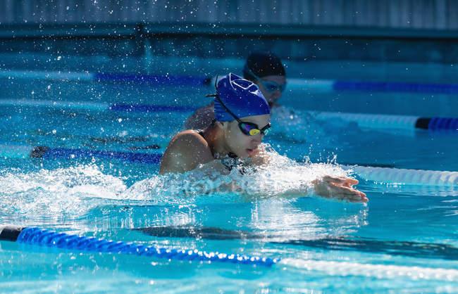 Вид сбоку на молодых пловцов, плавающих брассом вольным стилем в бассейне — стоковое фото
