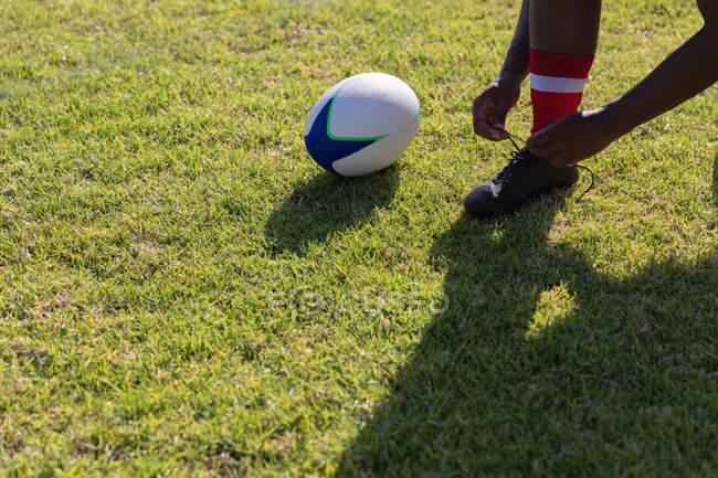Низький кут чоловічого регбіст, прив'язавши його на черевиках регбі землю на сонці — стокове фото