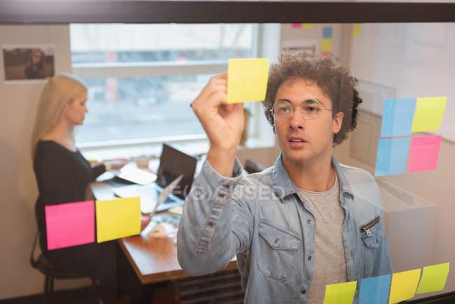Vue de face d'homme d'affaires caucasien écrit sur pense-bête dans office et femme d'affaires caucasien travaillant derrière lui — Photo de stock