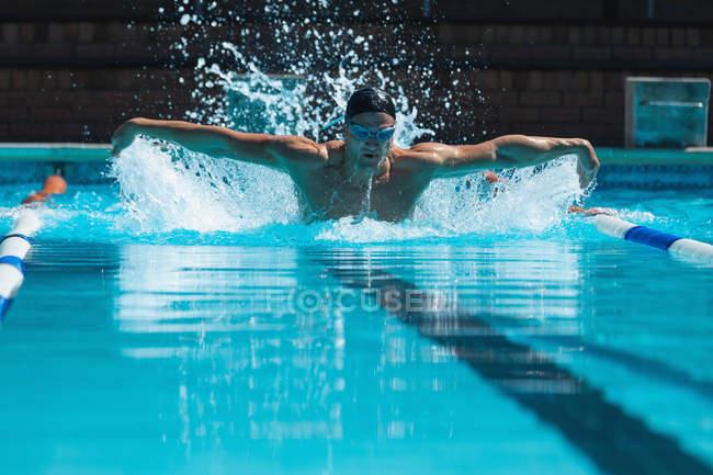 Вид спереди мужчины, плавающего в бассейне с купальщиком, плавающим бабочкой — стоковое фото