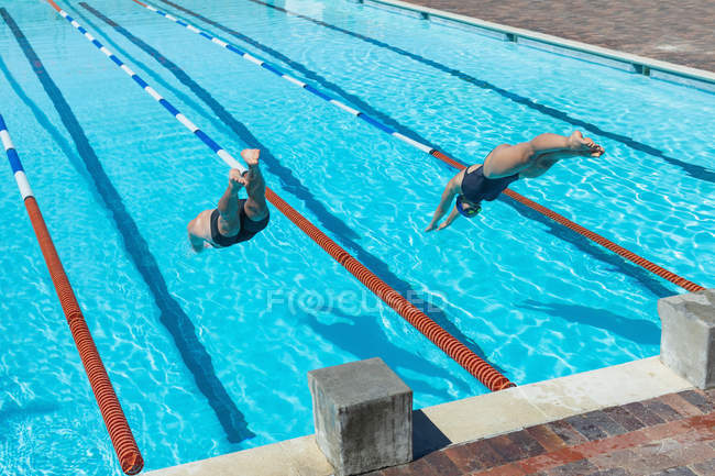 High angle view of male and female Caucasian swimmers jumping into water in the same time at the swimming pool in the sunshine — Stock Photo