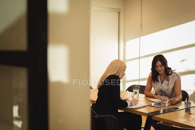 Vista frontal de las mujeres de negocios observando y trabajando sobre la tableta digital en la conferencia de oficina - foto de stock
