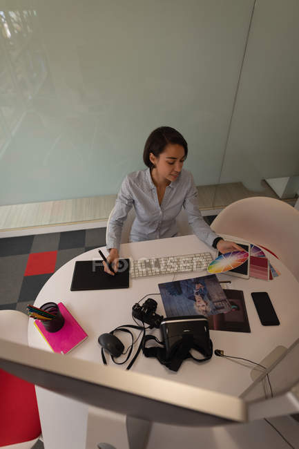 High angle view of an Asian graphic designer working over graphic tablet at desk in office — Stock Photo
