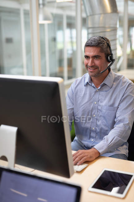Front view of businessman operating with his computer and a headset at desk in office — Stock Photo