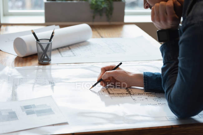 Mid section of businessman standing and working over blueprint at office conference — Stock Photo