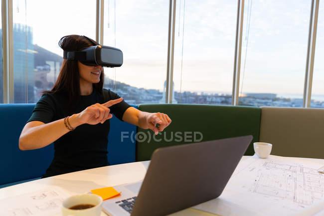 Vista frontal de la joven ejecutiva feliz usando auriculares de realidad virtual en una oficina moderna - foto de stock