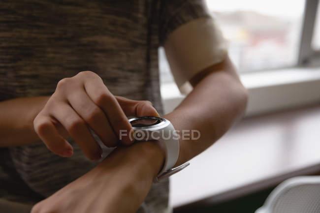 Sezione centrale della donna d'affari utilizzando orologio intelligente in ufficio — Foto stock