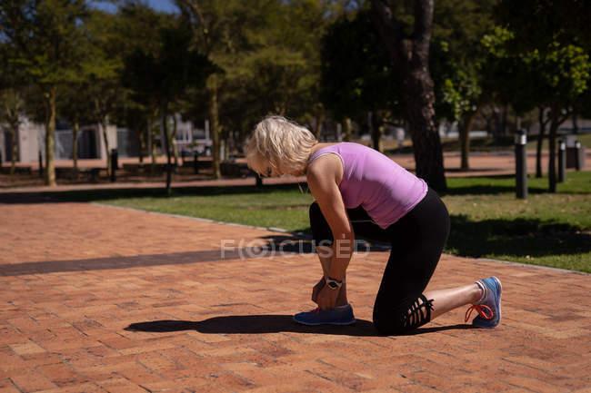 Seitenansicht einer aktiven senior Frau binden ihre Schnürsenkel im Park an einem sonnigen Tag — Stockfoto