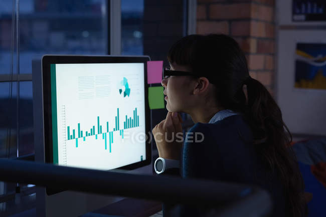 Side view of businesswoman working over graph project in office at desk by night — Stock Photo
