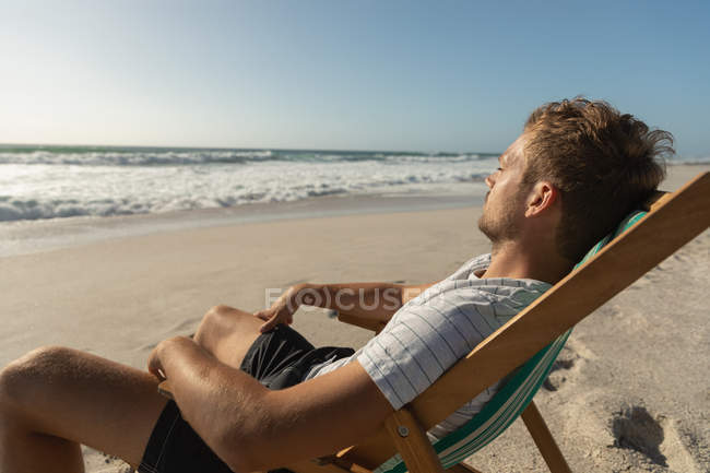 Side view of young man relaxing on sun lounger at beach. He is sitting facing of ocean - foto de stock