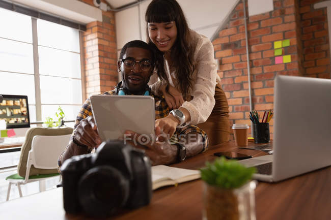 Low angle view of diverse business people discussing over digital tablet in office — Stock Photo