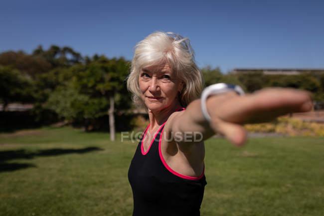 Vista lateral de uma mulher idosa ativa se exercitando no parque em um dia ensolarado — Fotografia de Stock