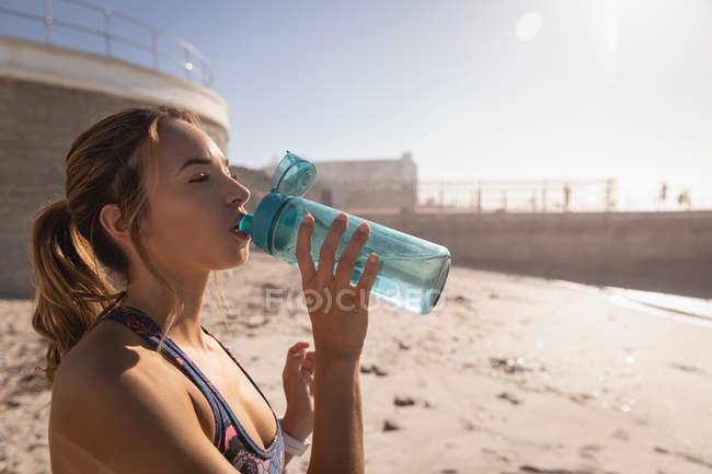 Vista laterale della donna che beve acqua con bottiglia mentre si trova in spiaggia in una giornata di sole — Foto stock