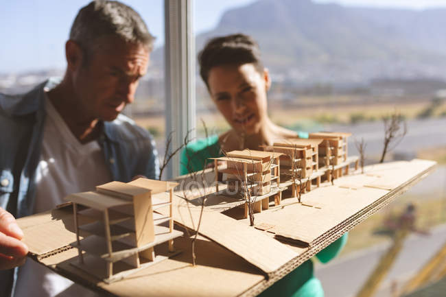 Front view of Caucasian architects discussing over architectural model at office against beautiful view — Stock Photo