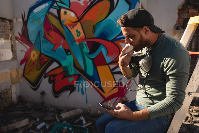 Side view of young Caucasian graffiti artist having food while using mobile phone — Stock Photo