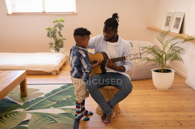 Front view of happy African-American father and son playing with guitar at home — Stock Photo