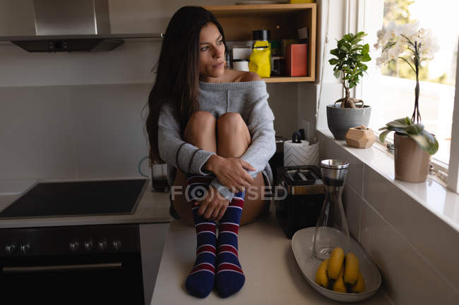 Front view of beautiful mixed-race woman relaxing in kitchen at home. She is looking away — Stock Photo