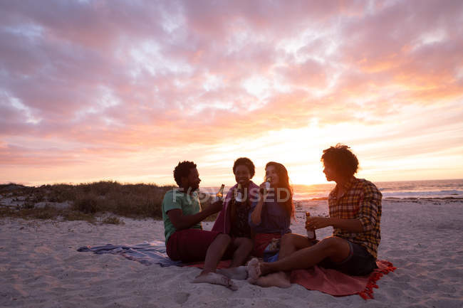Side view of multi-ethnic friends group interacting with each other while having beer at beach against sundown — Stock Photo
