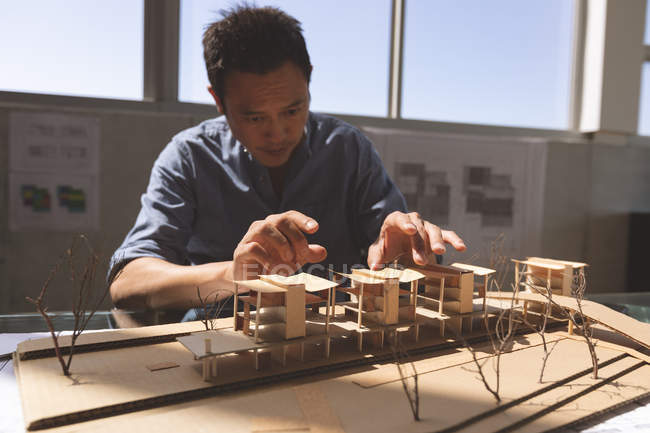 Front view of a male Asian architect working on an architectural building model at desk in a modern office — Stock Photo