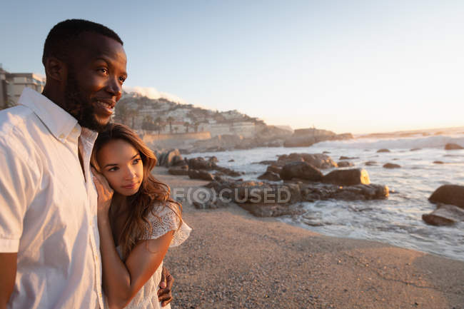 Side view of multi ethnic couple standing with arm around on the beach at sunset. They are soothed — Stock Photo