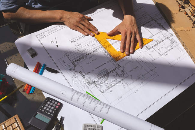 High angle view of male architect working on blueprint with triangle ruler at desk in a modern office — Stock Photo