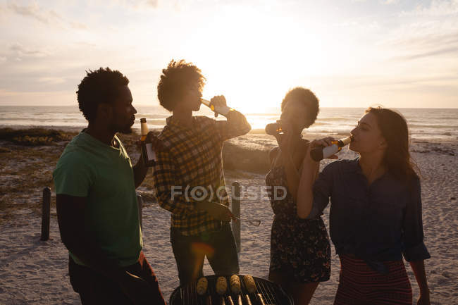 Front view of multi-ethnic friends group drinking beer together at beach against sunshine in background — Stock Photo