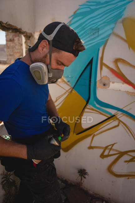 Side view of young Caucasian graffiti artist standing with spray painting at alley room — Stock Photo
