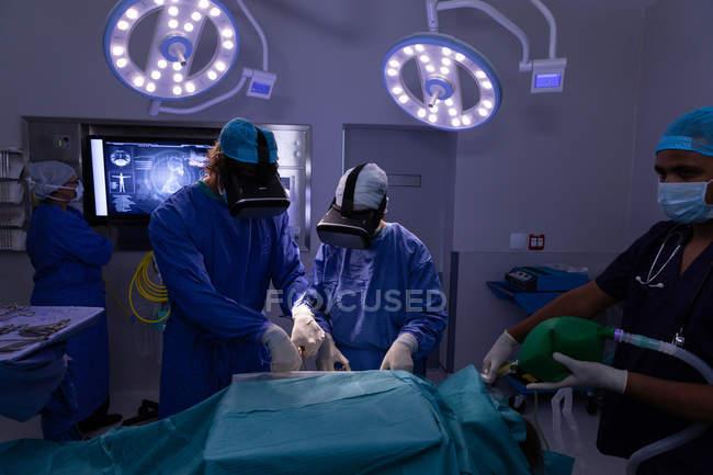 Frontansicht von Chirurgen mit Virtual-Reality-Headset während der Operation im Operationssaal des Krankenhauses — Stockfoto