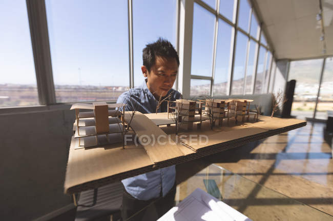 Front view of a male Asian architect holding an architectural building model and working on it at desk in a modern office — Stock Photo