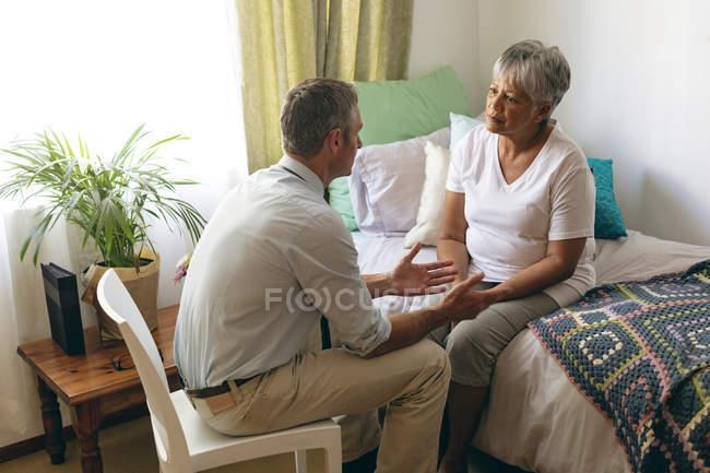 Erhöhte Ansicht des kaukasischen männlichen Arzt Interaktion mit senior Mischlinge Patientin im Altenheim — Stockfoto