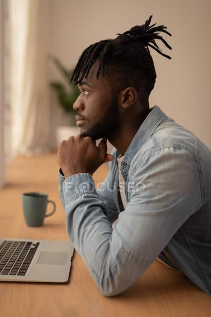 Вид збоку вдумливі афро-американських людини з ноутбуком, сидячи на стільці в домашніх умовах. Він дивлячись — стокове фото