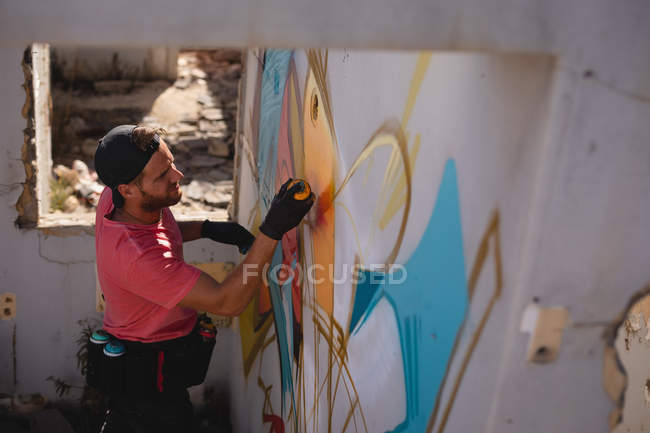 High angle view of young Caucasian graffiti artist spray painting on weathered wall room — Stock Photo