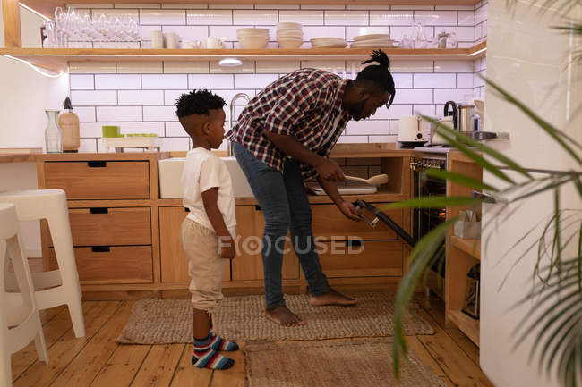 Side view of handsome African-American man inserting pizza in oven at home kitchen while his son standing at backward — Stock Photo
