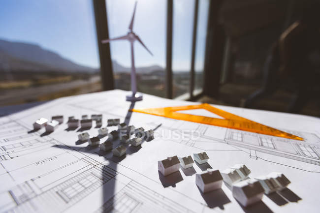 Close up of house model over blueprint with wind turbine model and a triangle ruler on desk in office — Stock Photo