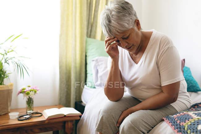 Вид спереди старший печально смешанной расы женщина, сидя на кровати, в домах престарелых. Женщина смотрит разочарование с рукой на лбу — стоковое фото
