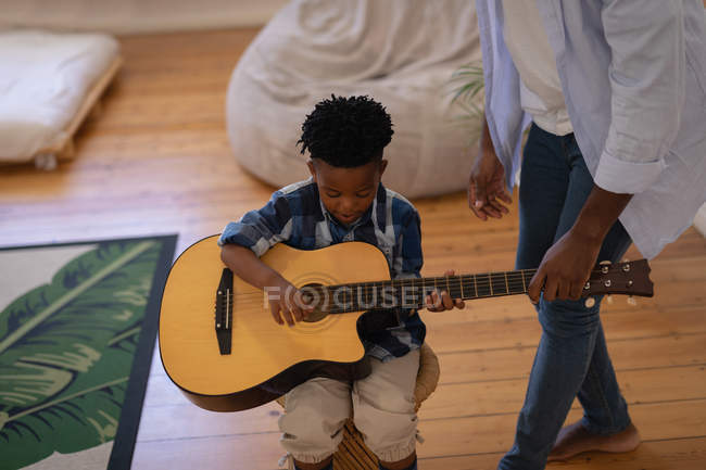 High angle view of African-American father assisting his son to play guitar at home — Stock Photo