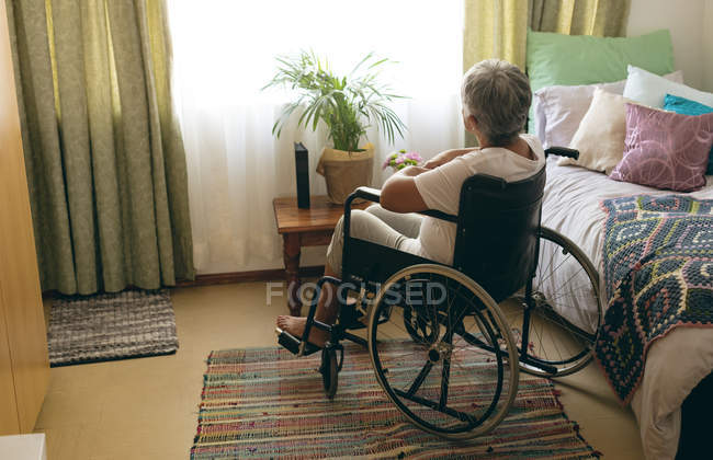 Rear view of thoughtful disabled senior woman siting in wheelchair in bedroom at retirement home — Stock Photo