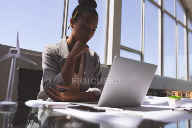 Niedrigen Winkel Ansicht der Mischlinge Geschäftsfrau mit Laptop am Schreibtisch im Büro — Stockfoto
