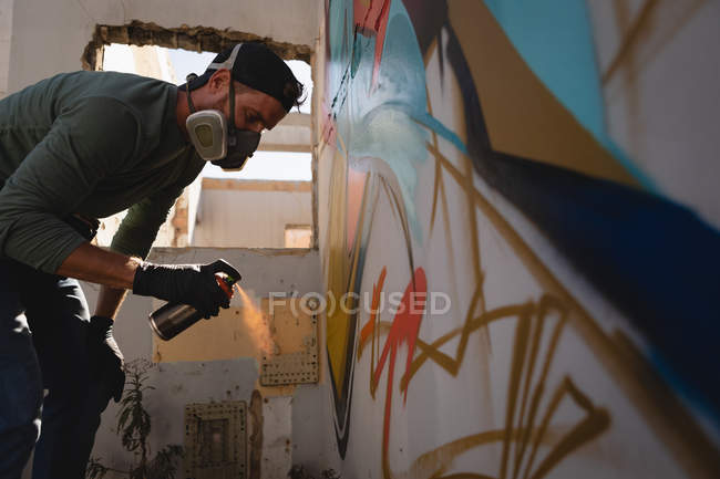 Low angle view of young Caucasian graffiti artist spray painting on weathered wall at alley — Stock Photo