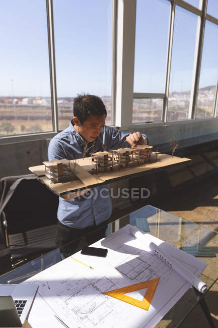Front view of male Asian architect holding an architectural building model and working on it at desk in a modern office — Stock Photo