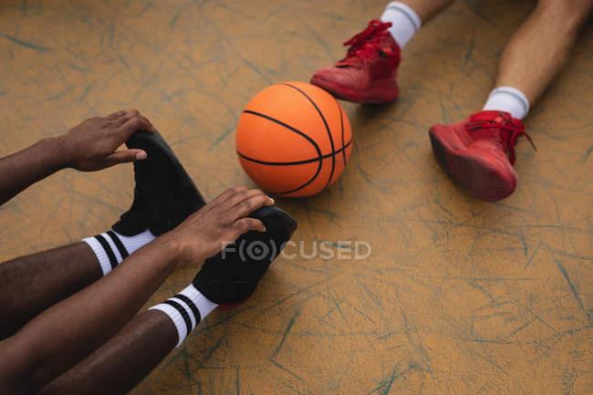 Низкая группа баскетболистов, сидящих и разогревающихся перед игрой на баскетбольной площадке — стоковое фото