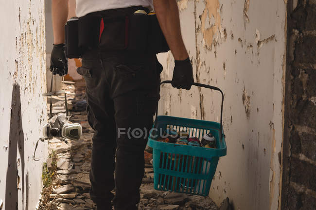 Rear view of graffiti artist walking with basket of spray paint at alley — Stock Photo
