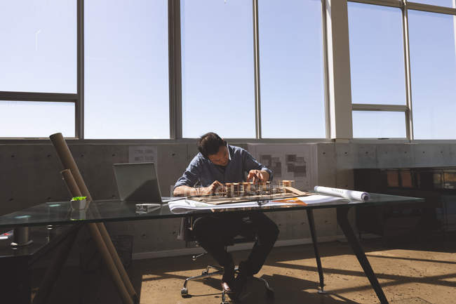 Front view of Asian male architect working on architectural model at desk in a modern office — Stock Photo