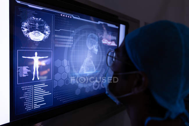 Side view of male surgeon looking at digital screen in operating room at hospital — Stock Photo