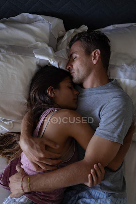 High angle view of romantic multi-ethnic couple sleeping on bed at home. they are hugging each other — Stock Photo