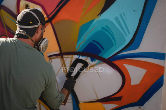 Rear view of young Caucasian graffiti artist spray painting on weathered wall room — Stock Photo